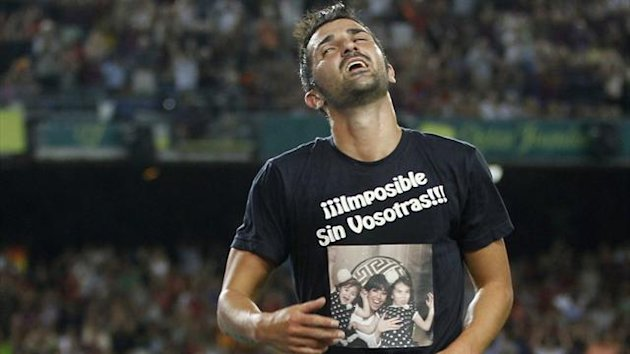 "Barcelona's David Villa celebrates his goal against Real Sociedad by wearing a T-shirt with a picture of his family, which reads: ""Impossible without you"""