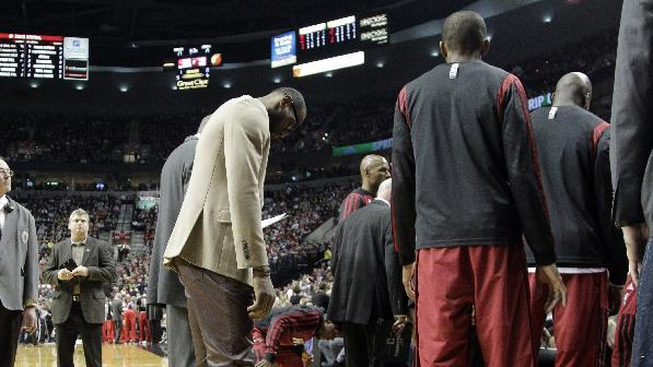 Miami Heat forward LeBron James stands at left as his team huddles before an NBA basketball game against the Portland Trail Blazers in Portland, Ore., Saturday, Dec. 28, 2013