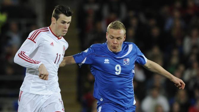 Wales' Gareth Bale is challenged by Iceland's Kolbeinn Sigthorsson during the friendly international soccer match at Cardiff City Stadium in Cardiff