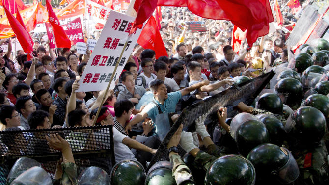 Chinese demonstrators clash with policemen at the barricades during an anti-Japan protests outside the Japanese Embassy in Beijing Saturday, Sept. 15, 2012. Angry protesters staged anti-Japanese demonstrations in cities across China Saturday over Japan's control of disputed islands, with a protest in Beijing turning violent before being brought under control by police. (AP Photo/Andy Wong)
