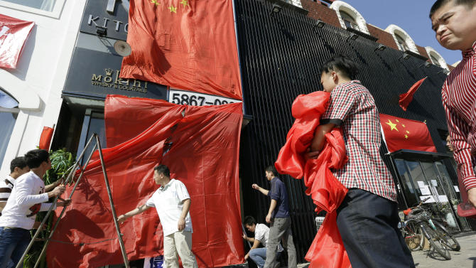 Workers at a Japanese restaurant cover up the shop front with Chinese national flags and red clothes ahead of major protests expected on Tuesday in Beijing, China, Monday, Sept. 17, 2012. Chinese are trying to hurt Japan economically for leverage in a bitter dispute over contested islands, turning to angry protests and calls for boycotts of Japanese businesses, abetted in part by China's government.  (AP Photo/Ng Han Guan)