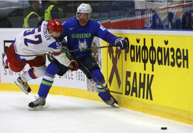 Russia's Shirokov falls as he fights for the puck with Slovenia's Kovacevic during their Ice Hockey World Championship game at the CEZ arena in Ostrava