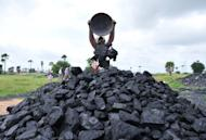 Labourers pile up coal at a coal field on the outskirts of Hyderabad, southern India, on September 5, 2012. Coal is set to surpass oil as the world's top fuel within a decade, driven by growth in emerging market giants China and India, with even Europe finding it hard to cut use despite pollution concerns, according to a report published Tuesday