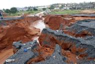 A road washed away by torrential rainfall in the Mozambican capital Maputo is pictured on January 15, 2013. Flooding in Mozambique has killed at least 17 people and displaced tens of thousands more, according to United Nations figures, with a fresh storm surge feared Friday