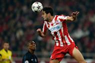 Manchester United's Ashley Young (L) looks on as Olympiakos' Ivan Marcano heads the ball during their UEFA Champions League round of 16 first leg match, at the Karaiskaki stadium in Athens, on February 25, 2014