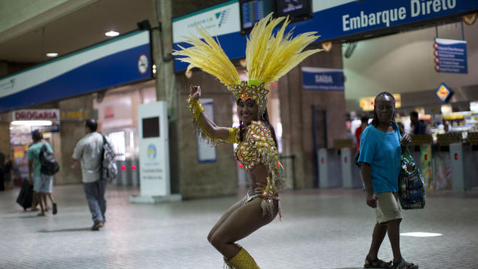 "In this photo taken Saturday, Feb. 2, 2013, samba dancer Diana Prado performs during a carnival parade at central station in Rio de Janeiro, Brazil. Prado spends her daylight hours working as a supervisor at a call center. At night, she is a samba dancer, or ""passista,"" as they're known in Portuguese. Prado made her Carnival debut at age 19, after auditioning for a spot with the Sao Clemente, one of 13 top-tier schools that will compete for the annual titles at the Sambadrome this weekend. (AP Photo/Felipe Dana)"