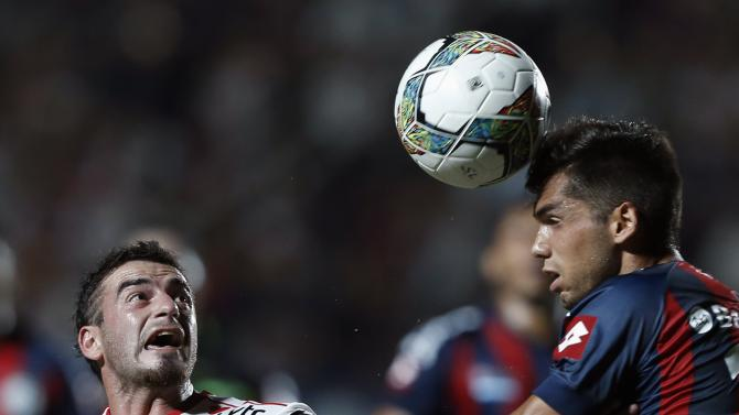 Mas of Argentina's San Lorenzo heads the ball under pressure by Salom of Chile's Union Espanola during their Copa Libertadores soccer match in Buenos Aires