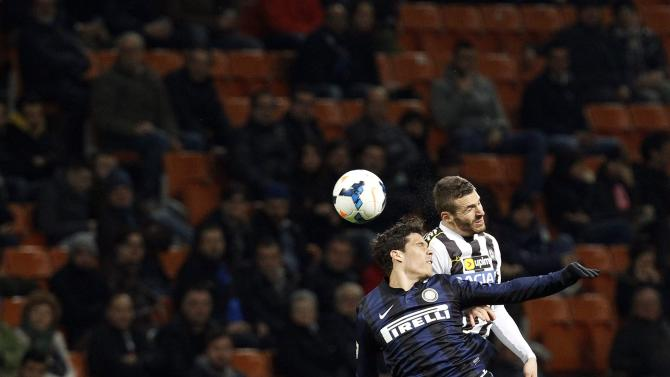 Inter Milan's Hernanes jumps for the ball with Udinese's Heurtaux during their Italian Serie A soccer match at San Siro stadium in Milan