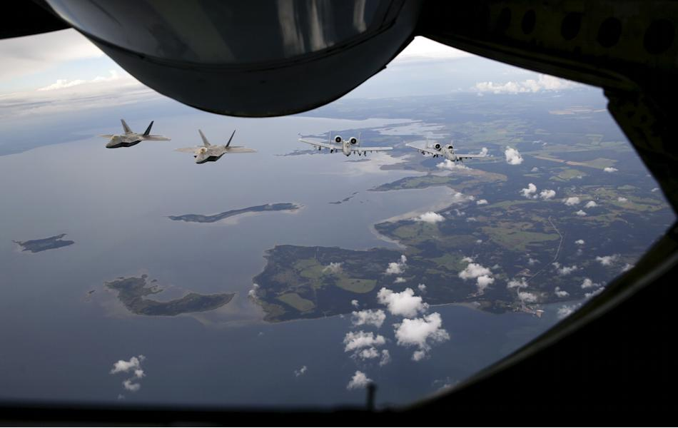 Two F-22 Raptor fighter jets and two A-10 Thunderbolt approach a KC-135 Stratotanker near the Estonian capital of Tallinn