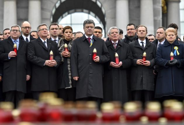 Ukraine'sPoroshenko, with local and foreign politicians, hold candles during a memorial rally to commemorate people who were killed during the uprising on Maidan square a year ago, in Kiev
