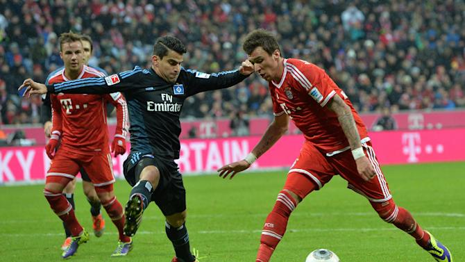 Bayern's Mario Mandzukic of Croatia, right, and Hamburg's Hernandez Rincon , center, challenge for the ball   during  the German first division Bundesliga soccer match between FC Bayern Munich and Hamburger SV  in Munich, Germany, Saturday, Dec. 14, 2013