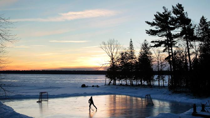 A youth plays pond hockey as the sun rises on Pigeon Lake in the region of Kawartha Lakes Ontario.