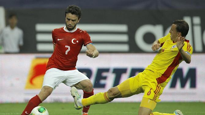 Turkey's Gokhan Gonul, left, challenges for the ball with Romania's Vlad Chiriches during a World Cup Group D qualifying soccer match between Romania and Turkey at the National Arena stadium in Bucharest, Romania, Tuesday, Sept. 10, 2013