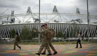 British military personnel walk past the Olympic Stadium ahead of the London 2012 Olympic Games in the Olympic Park in east London