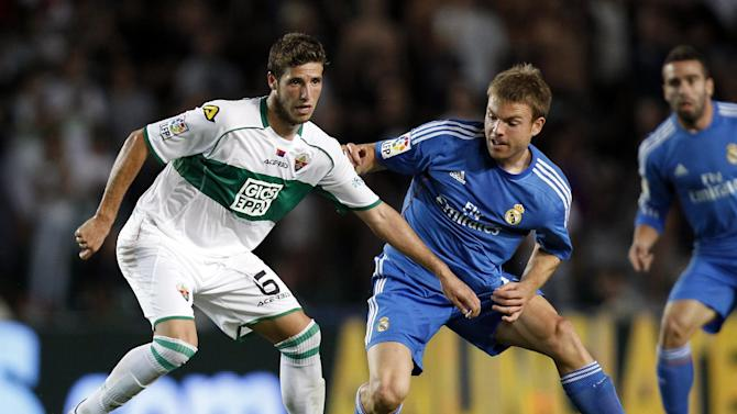 Real Madrid's Asier Illarramendi, right, duels for the ball with Elche's  Ruben Perez del Marmol  during their La Liga soccer match at the Martinez Valero stadium in Elche, Spain, Wednesday, Sept. 25, 2013