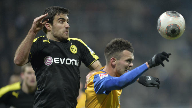 Dortmund's Sokratis of Greece, left, and Braunschweig's Orhan Ademi of Switzerland, right, challenge for the ball during the German Bundesliga soccer match between Eintracht Braunschweig and Borussia Dortmund in Braunschweig,  Germany, Friday, Jan. 31, 2014