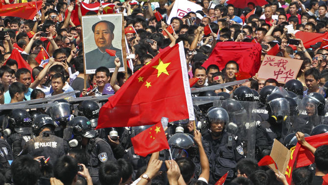 Chinese demonstrators raise national flags as they confront riot policemen during a protest against Japan in Shenzhen, China Sunday, Sept. 16, 2012. Protesters in China began another day of demonstrations against Japan, after protests over disputed islands spread across numerous cities and at times turned violent. (AP Photo/Apple Daily) HONG KONG OUT, TAIWAN OUT, NO SALES