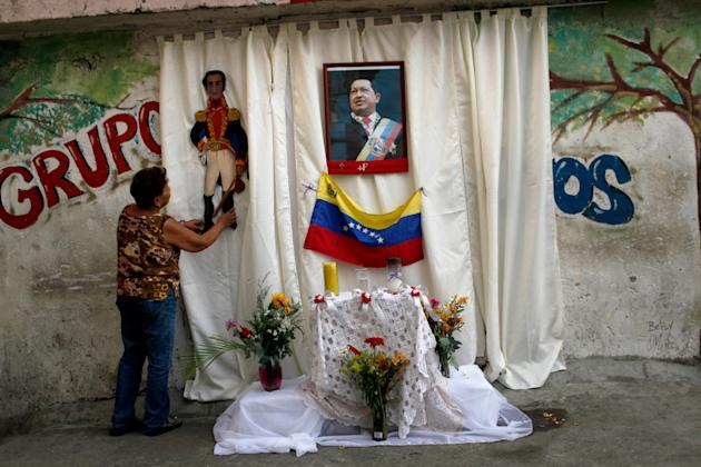 A woman places an image of Venezuela's independence hero Simon Bolivar on an altar set up on a sidewalk in honor of late President Hugo Chavez, whose picture hangs on the curtain, along a street where