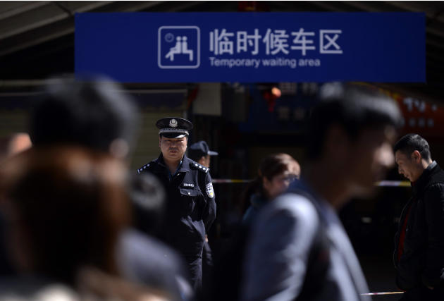 A policeman stands guard near a cordoned area outside Kunming Railway Station in Kunming, in western China's Yunnan province Sunday, March 2, 2014. More than 10 assailants slashed scores of people wit