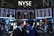 Traders work on the floor of the New York Stock Exchange. World stock markets mostly fell on Friday after the economic outlook in Germany soured sharply, with bank shares in focus after Moody's downgraded some of the biggest names including HSBC