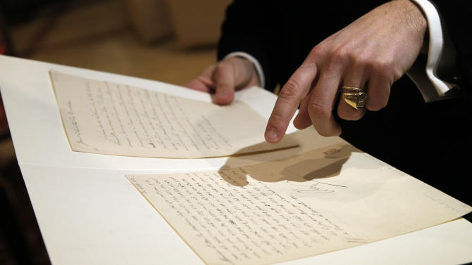 "In this photo taken Wednesday, Nov. 28, 2012, auction house associate Jean-Christophe Chataigniera holds up a letter dictated and signed by Napoleon in secret code that declares his intentions ""to blow up the Kremlin"" during his ill-fated Russian campaign is displayed in Fontainebleau, outside Paris. The rare letter, written in unusually emotive language, sees Napoleon complain of harsh conditions and the shortcomings of his grand army. The letter goes on auction Sunday, Dec. 2, 2012. (AP Photo/Christophe Ena)"