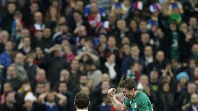 Ireland's rugby team players, right, celebrate after defeating France and winning the Six Nations Rugby Union tournament at the Stade de France stadium, in Saint Denis, outside Paris, Saturday, March 15, 2014
