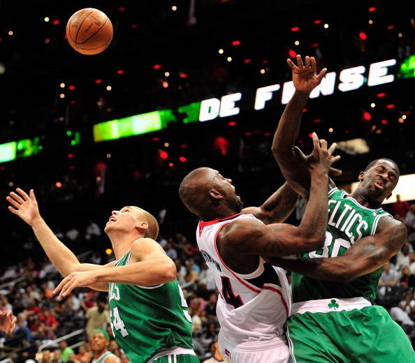 Ivan Johnson #44 of the Atlanta Hawks battles for a rebound with Greg Stiesma #54 and Brandon Bass #30 of the Boston Celtics in Game One of the Eastern Conference Quarterfinals in the 2012 NBA Playoff