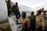 "Foreigners captured by Sudanese military in the Heglig oilfield area April 28, are escorted off an airplane in Khartoum. The British embassy was ""urgently"" investigating on Sunday the arrest in Sudan of one of its citizens, who was among four foreigners the Sudanese military said it captured in the tense Heglig oil region"