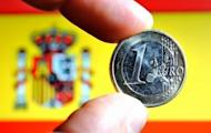 A euro coin held before the Spanish flag. Spanish borrowing costs roared to a euro-era record high Tuesday on a market beset by doubts over a vast rescue loan for the country's banks and by fears of a Greek exit from the eurozone