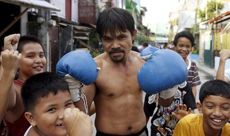 World Boxing champion Manny Pacquiao look-alike Johnny Dagami poses before photographers at his neighbourhood in Las Pinas, Metro Manila