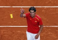 Spain's Rafael Nadal throws his wristband to the public after winning against Ukraine at the end of their Davis Cup World Group playoff tennis tie in Madrid September 14, 2013. REUTERS/Sergio Perez (SPAIN - Tags: SPORT TENNIS)