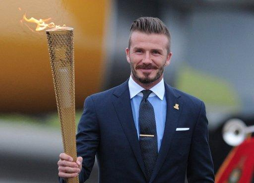 David Beckham carries the Olympic torch as it arrives at RNAS Culdrose air base in Cornwall on May 18, 2012