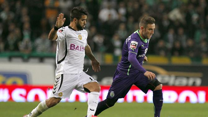 Sporting's Diego Capel, right, from Spain, tries to sidestep Nacional's Daniel Candeias during the Portuguese league soccer match between Sporting and Nacional at the Alvalade stadium in Lisbon, Saturday, Dec. 21, 2013. The match ended in a 0-0 draw