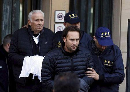 Argentine businessmen Jinkis and Hugo Jinkis who are wanted by U.S. prosecutors in a FIFA bribery investigation, are escorted by police officers after they turned themselves in on to authorities in Buenos Aires