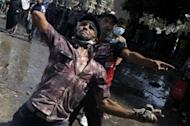 Egyptian protesters throw stones to the riot police during clashes near the US embassy in Cairo