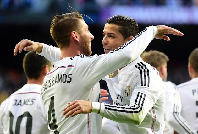 Real Madrid's Sergio Ramos (L) is congratulated by teammate Cristiano Ronaldo after scoring during the Spanish league match against Malaga in Madrid on April 18, 2015