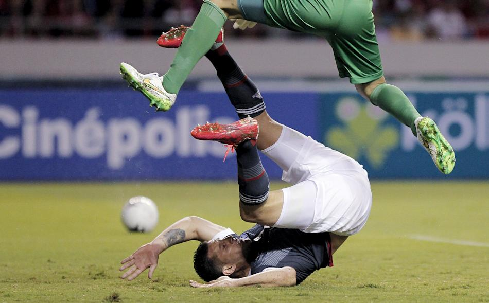 Goalkeeper Keylor Navas of Costa Rica jumps over Raul Bobadilla of Paraguay during their international friendly soccer match at the National Stadium in San Jose