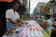 A vendor (L) sells local journals and newspapers on a roadside in Yangon on August 20, 2012. Myanmar will allow private newspapers to publish daily from April 1, ending a decades-old ban in a further easing of the country's draconian censorship regime, the government said Friday