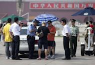 Police, plainclothes police, and paramilitary guards check photos taken by a man on Tiananmen Square in Beijing. Hong Kong held a candlelight vigil Monday to mark the 23rd anniversary of the Tiananmen Square crackdown, in stark contrast to mainland China where activists said hundreds of people were detained