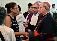 Cuban Cardinal Jaime Ortega (R) greets Ofelia Acevedo (L), the widow of Cuban dissident Oswaldo Paya, on July 24, during his funeral in Havana. Acevedo rejected a government report that blamed the car crash that killed her husband and a fellow dissident on the vehicle's driver