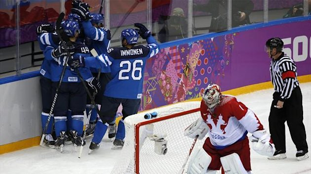 Finland's Mikael Granlund (L, obscured) and his linemates celebrate after his goal against Russia's goalie Semyon Varlamov (C) during the second period of their men's quarter-finals ice hockey game at the 2014 Sochi Winter Olympic Games, February 19, 2014