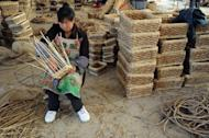A woman weaves rattan baskets for sale at a shop in Hefei, east China's Anhui province in June 2012. China's exports for June were $180.21 billion, up 11.3 percent year-on-year, while imports rose 6.3 percent to reach $148.48 billion, the General Administration of Customs said in a statement