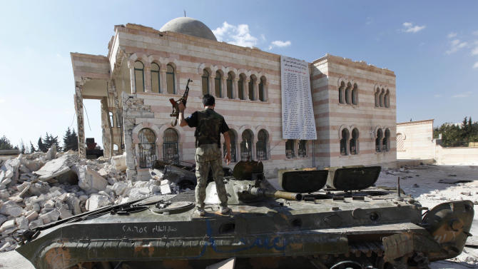 A Free Syrian Army soldier stands on a damaged Syrian military tank in front of a damaged mosque, which were both destroyed during fighting with government forces, in the Syrian town of Azaz, on the outskirts of Aleppo, Sunday, Sept. 23, 2012. Syria's bloody 18-month conflict, which activists say has killed nearly 30,000 people, has so far eluded all attempts at international mediation. (AP Photo/Hussein Malla)