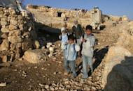"Palestinian children leave Tuba village in the Hebron hills to go to school. Three Israeli settlers in their 20s are alleged to have driven to al Asja in the southern Hebron hills on December 2, set a car on fire and sprayed ""price tag"" and ""Mazal Tov"" (congratulations) on a nearby wall"