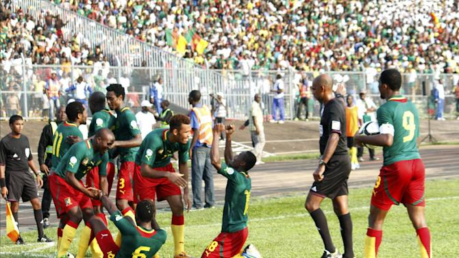 Cameroon national soccer team players celebrate after scoring in their World Cup qualifying playoff second leg soccer match, in Yaounde, Cameroon, Sunday, Nov. 17, 2013. Cameroon qualified Sunday for the 2014 World Cup in Brazil with a resounding 4-1 win over Tunisia in the second leg of their playoff