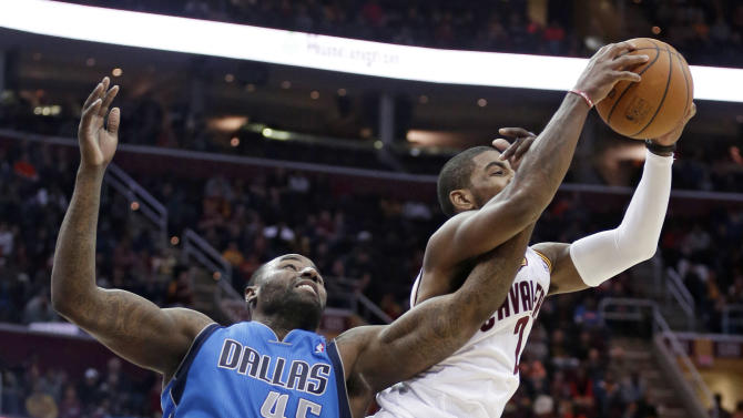 Dallas Mavericks' DeJuan Blair (45) fouls Cleveland Cavaliers' Kyrie Irving during the fourth quarter of an NBA basketball game, Monday, Jan. 20, 2014, in Cleveland. Dallas defeated Cleveland 102-97