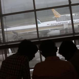 People sit at a viewing gallery overlooking a Singapore Airlines plane sitting next to SilkAir and Scoot planes at Changi Airport in Singapore