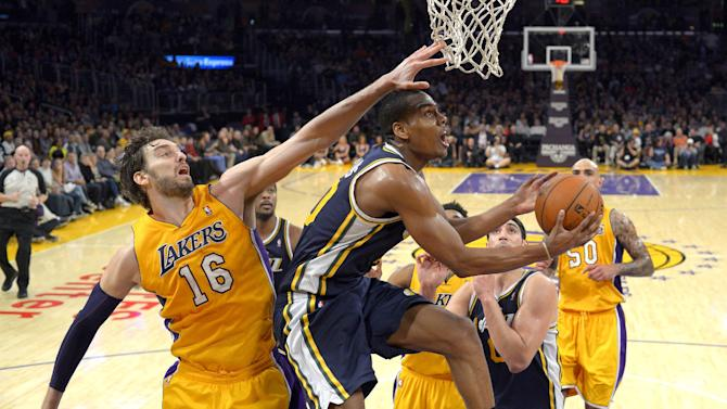 Utah Jazz guard Alec Burks, right, puts up a shot as as Los Angeles Lakers center Pau Gasol, of Spain, defends during the second half of an NBA basketball game, Friday, Jan. 3, 2014, in Los Angeles