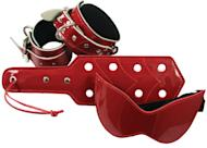 "This product image released by Babeland shows a blindfold, a paddle and wrist and ankle restraints in red patent leather. Sales are roof-raising for Babeland since the surge in popularity from E L James' ""Fifty Shades of Grey"" book series. With three adult toy stores in New York, one in Seattle and a website, co-founder Claire Cavanah reports a 40 percent uptick in business overall, with eye-popping increases for bondage toys.(AP Photo/Babeland)"