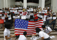 "Student activist Marjohara Tucay, right foreground, who heckled U.S. Secretary of State Hillary Rodham Clinton during her town hall meeting and interview in Manila Wednesday, leads other student leaders in burning a mock American flag during a ""nationally coordinated U.S. flag-burning"" to protest alleged unequal U.S.-Philippines relations Thursday Nov. 17, 2011 at the University of the Philippines campus in Diliman, Quezon city northeast of Manila. On Thursday, Philippine Defense Secretary Voltaire Gazmin said the United States will provide a second warship to the ill-equipped Philippine military as its longtime Asian ally confronts China in increasingly territorial disputes in the South China Sea. (AP Photo/Bullit Marquez)"